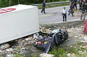 KNUST UNDER HENGEREN: Volvoen lå smadret under hengeren som var fullastet med 30 tonn returpapir. Her har redningsmannskapene dratt bilen løs for å få ut de omkomne.