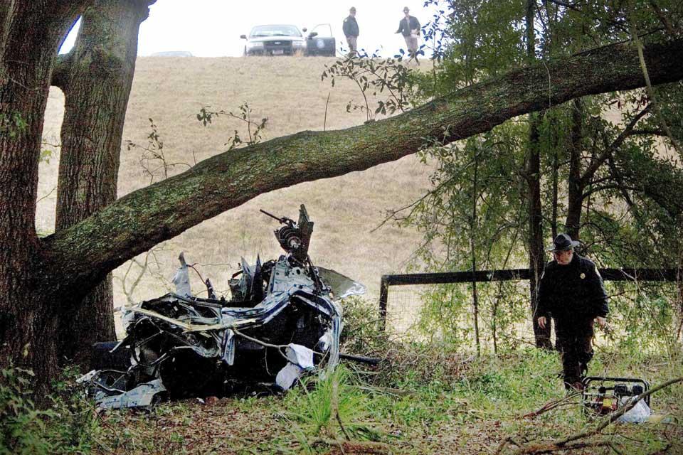 FULLSTENDIG KNUST: En politimann gransker restene av BMW-en Joshua Ammirato (18) presset til det ytterste før den bokstavelig talt tok av fra flystripa på Greystone flyplass og traff et eiketre fem meter over bakken.