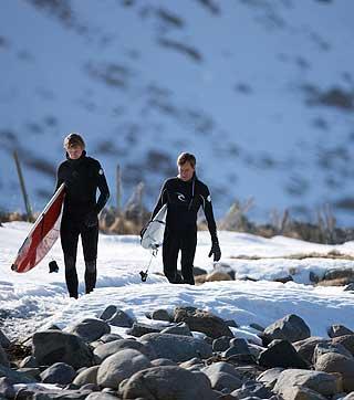 VÅTDRAKT MED VARMEELEMENTER: Lokale Tommy Olsen som driver camping og surfutleie og Tom Curren på vei ut i vannet.