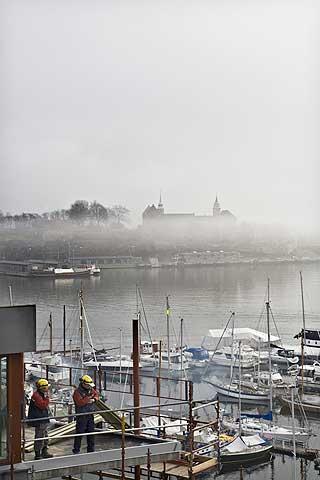 Ut av tåka: Etter å ha vært en anonym halvøy innerst i havnebassenget i Oslofjorden, bygges nå «nye» Tjuvholmen. Alt skal stå ferdig i 2012 - med den verdensberømtearkitekten Renzo Pianos nye kunstmuseum ytterst mot Akershus festning.