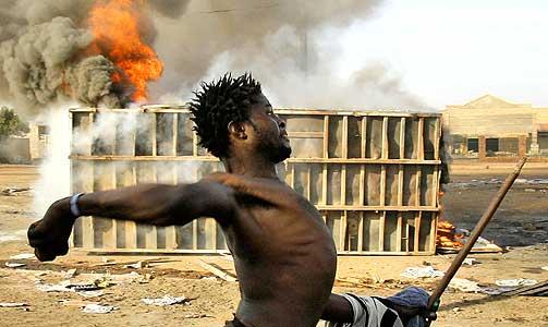 UNGE, FRUSTRERTE MENN: En mann kaster stein i gatekampene i Johannesburg.