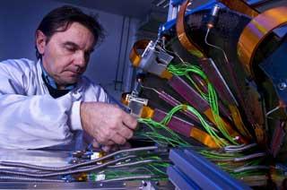 SISTE INNSPURT: En ingeniør monterer en av de siste delene av det gigantiske puslespillet som utgjør verdens største partikkeaksellerator. Foto: CERN