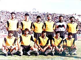 FOR SADDAM:  Saad Keis Naoman (I f�rste rekke til h�yre), spilte I flere �r for laget til Saddams s�nn, Uday. Her poserer han sammen med resten av spillerne p� Al-Rasheed p� slutten av 80-tallet. Bak p� tribunen ruver en kjempeplakat av Saddam selv.